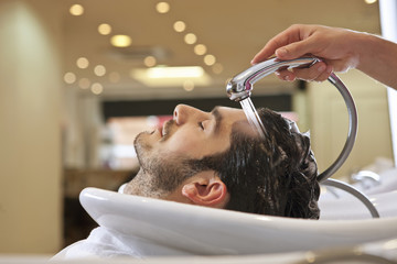 A male hairdresser rinsing a male clients hair