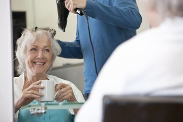 A senior woman with hot drink having her hair dried