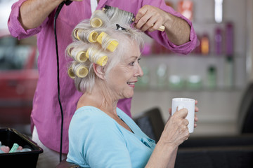 A senior woman having a hot drink whilst having her hair dried