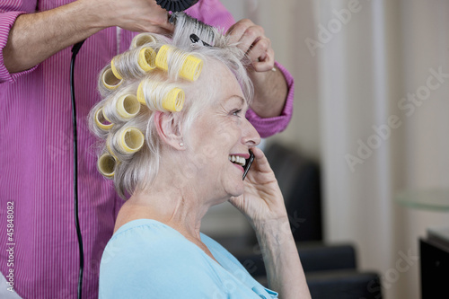 A senior woman talking on a mobile phone at the hairdressers