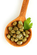 green capers in wooden spoon on white background close-up