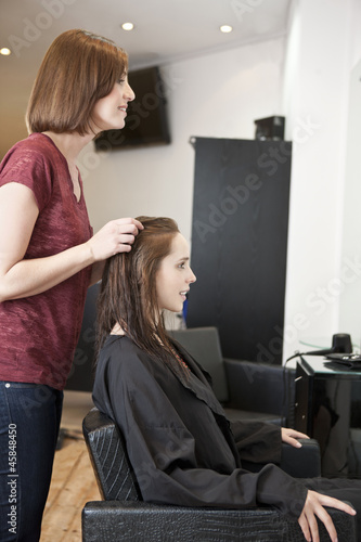 A female hairdresser discussing a female clients hair