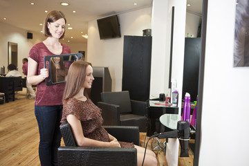 Client sees her new haircut in a mirror held by hairdresser