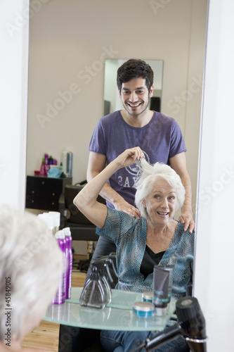 A female client discussing her hair with a male hairdresser