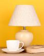 table lamp with cup and book on yellow background