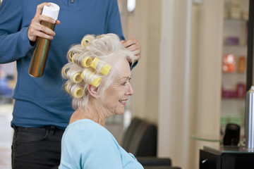 Male hairdresser applying hairspray to womans hair, close up