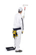 construction worker in white overalls with paint roller paint wa