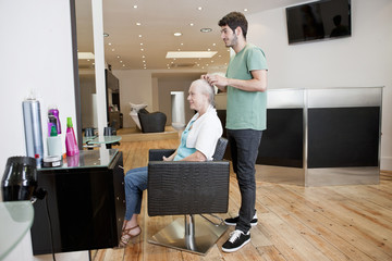 A male hairdresser applying product to his female clients hair