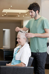 A male hairdresser combing a female clients hair