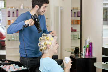 A male hairdresser drying a female clients hair