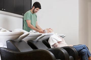 A male hairdresser shampooing a female clients hair