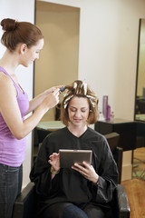 A woman having highlights in a salon and using a digital tablet