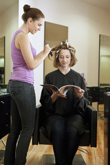 Woman having her hair coloured in a salon and reading a magazine
