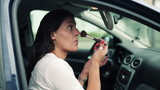 Woman applying beauty make-up in the car, steadicam shot