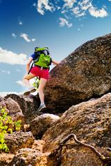 Woman climbs over a rock