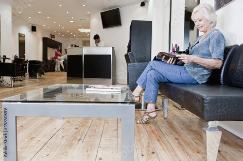 A senior woman reading a magazine at a hairdressers