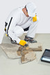 worker brush primer grout of stones