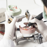 Fototapety Dental technician working with articulator