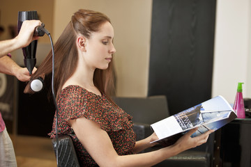A female client looking at a magazine in a hairdressing salon