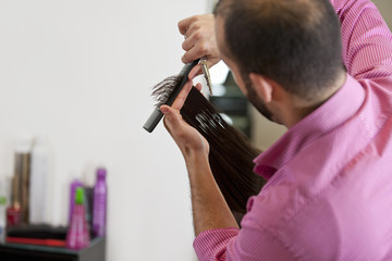 Male hairdresser cutting female clients' long hair, close up