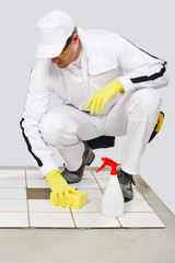 worker cleans with sponge and spray old tiles floor before tilli