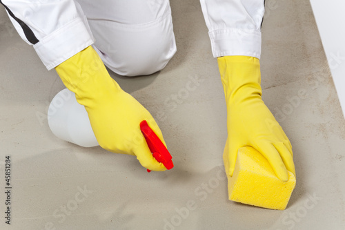worker clean cement substrate with sponge