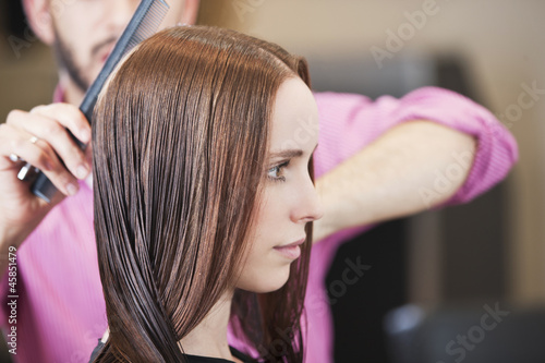A male hairdresser combing his female clients long hair