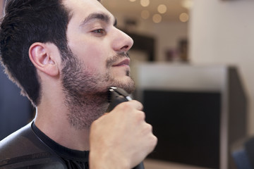 A male client having his facial hair trimmed, close up