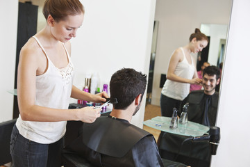 A female hairdresser cutting male clients hair with scissors