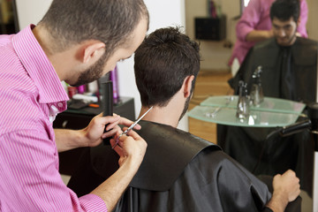 A male hairdresser cutting his male clients hair with scissors