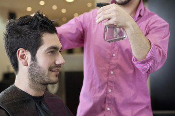 A male hairdresser spraying water on a male clients hair