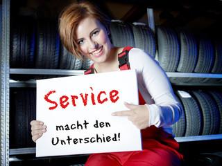Female car mechanic presents white message board in a tire stock