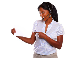Young woman wearing headphones holding white card