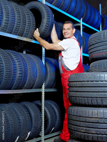 Car mechanic stores winter tire in a warehouse for tires