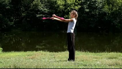 Гимнастка проводит тренировку с булавами на природе