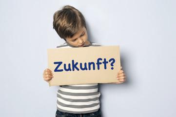 Kind mit Schild fragt nach seiner Zukunft