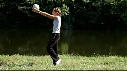 Гимнастка проводит тренировку с мячом на природе