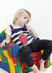 Little girl in a colorful armchair