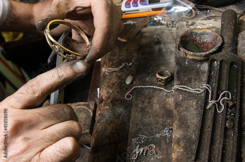 Goldsmith working on a bracelet with his aged hands