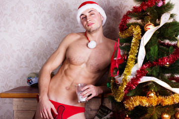 Young man near fireplace wearing Santa cap. Christmas