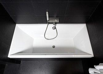 White square bathtub in modern black and white bathroom interior