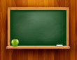 Blackboard with green apple on wood background.