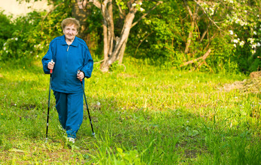 Active woman (85 years old) nordic walking outdoors.