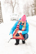 Woman put reflector triangle car breakdown winter