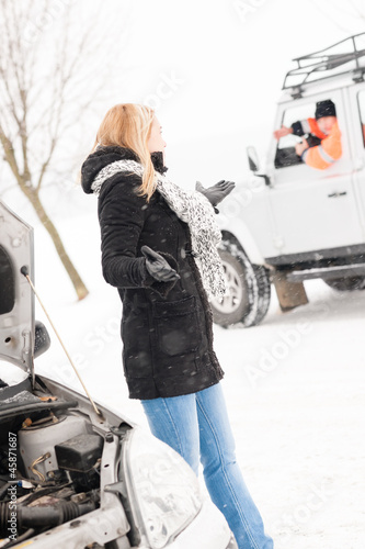 Woman having trouble with car snow assistance