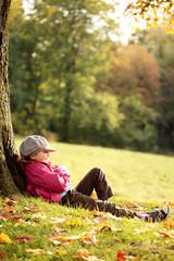 Mädchen relaxed im Park unter einem Baum