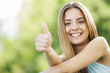 Happy young woman showing thumbs up sign