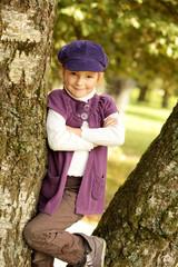 Kleines Mädchen lehnt am Baum und lacht