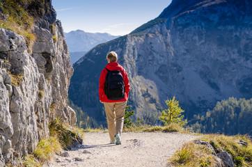 Frau in roter Jacke wandert in den Bergen