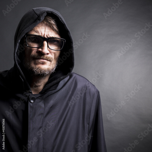 portrait of a man with a beard wearing glasses and hood